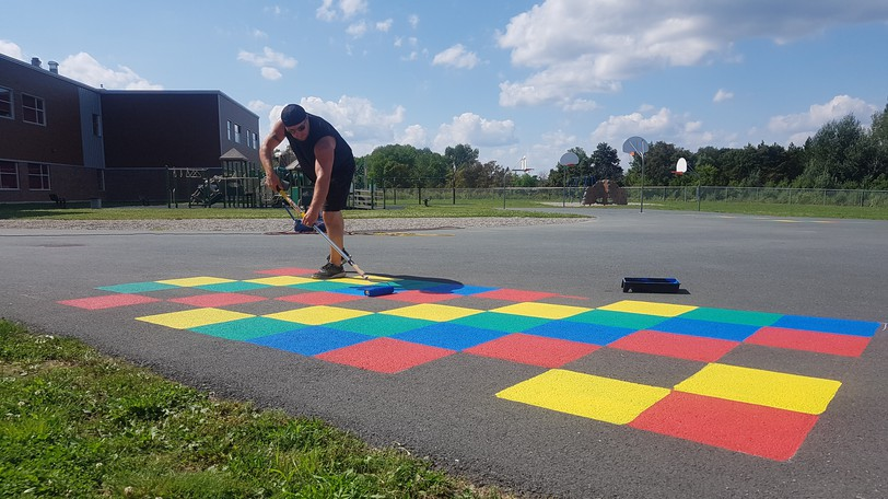 Artist Allie Howe began painting 3D art and games on the pavement of schools in the Anglophone North School District last week.