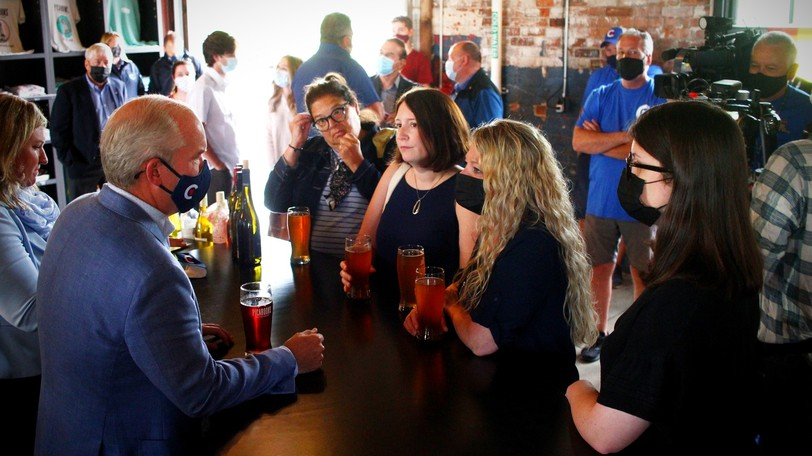 Erin O'Toole, left, takes on a pre-noon beer with party faithful and the cameras.