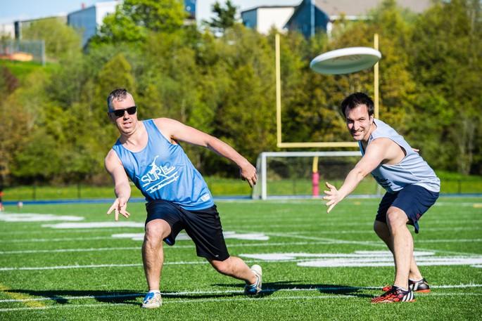 Jeff Brewer, left, flicks the disc past defender and Saint John Ultimate president Stephen Koval during a pick-up ultimate Frisbee game at Shamrock Park.