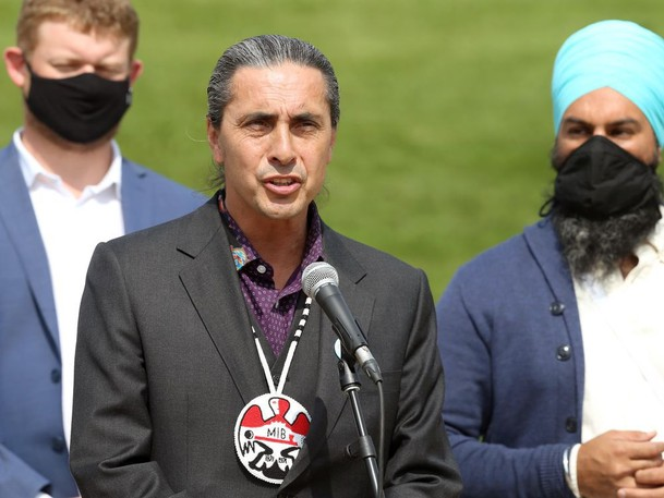 Arlen Dumas, Grand Chief of the Assembly of Manitoba Chiefs, takes the microphone during a media event for  federal NDP leader Jagmeet Singh (right) at Oodena Circle at The Forks in Winnipeg on Thurs., Aug. 26, 2021. At left is NDP MP Daniel Blaikie (Elmwood-Transcona).