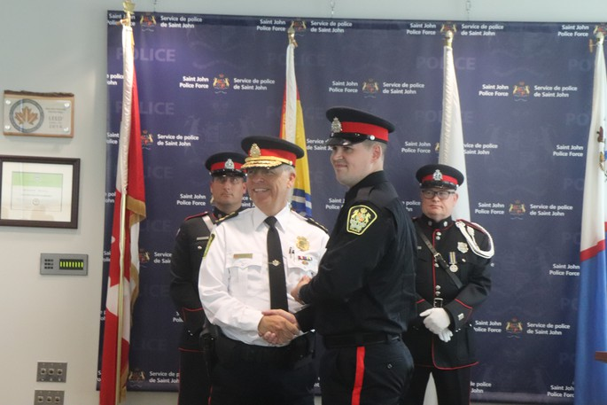 Saint John police Chief Robert Bruce hands new recruits their badges Friday.