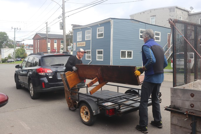 Ascent NB president Greg Hughes assisting in loading a pew to a small trailer.