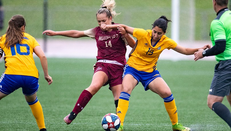 Mount Allison Mounties' Kayli Strickland (No. 14) and Universitéde Moncton Aigles Bleues' Leila Karam (No. 19) battle for the ball during an AUS women's soccer exhibition game on Saturday at Croix Bleue Medavie Stadium. Looking on is UdeM's Natalie Fleming, left.