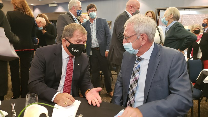 Former premier Frank McKenna, left, and Premier Blaine Higgs chat after the two men announced millions in funding to the University of New Brunswick for a new digital institute.