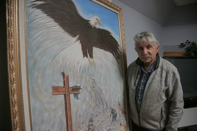 Saint John artist Norman Jackson stands by the original oil painting he created after the tragic 9/11 terrorist attacks on Tuesday, Sept. 11, 2001. To mark the 20th anniversary on Saturday, Jackson is heading to Gander, Newfoundland, where he will donate the painting to an art gallery in one of the small towns that helped roughly 7,000 passengers on 38 jetliners bound for the United States but rerouted due to the attacks.