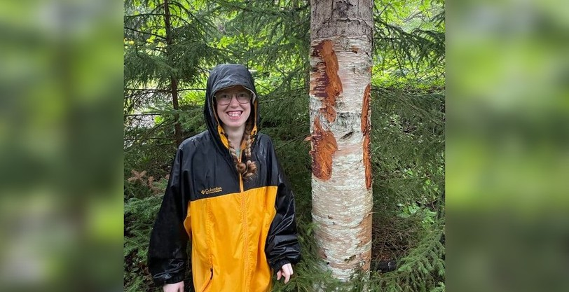 Maren Mealey stands next to a tree covered in large claw marks that was found at her campsite in Fundy National Park. She believes a bear had slept under her hammock while her family was staying in a tent.