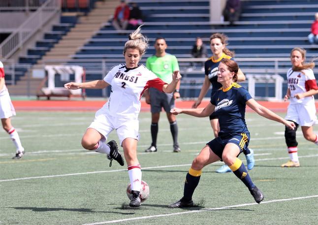 UNBSJ women's soccer team co-captain Makayla Martin, left, battles for a ball against Crandall University in pre-season action at the Canada Games Stadium.