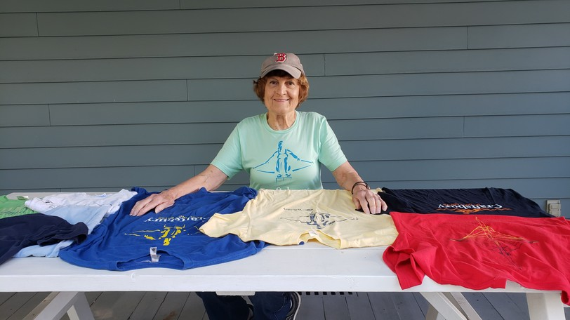 Eighty-one-year old Anne-Marie Taylor of Fredericton, shown with some of the T-shirts from the camp,  started going to a Vermont rowing camp every year when she turned 70.