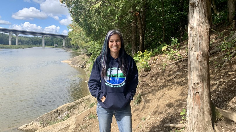 Meduxnekeag River Association Outreach and Marketing Coordinator Holly Melanson stands on the river bank on the Woodstock property the association and NB Power are collaborating to conserve.
