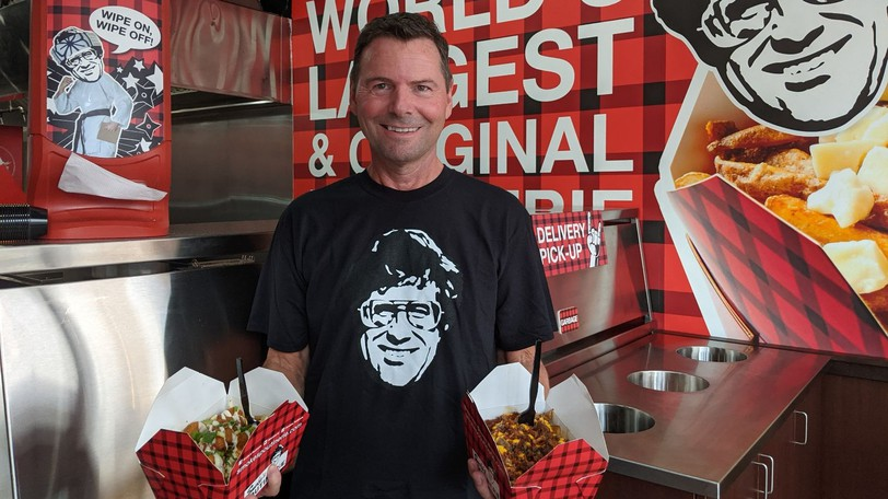 Wade Bruce, owner of Smoke's Poutinerie Moncton, holds a bacon cheeseburger and buffalo cauli-ranch poutine inside his restaurant last Friday. Smoke's Poutinerie is now open and located at 827 Main St.