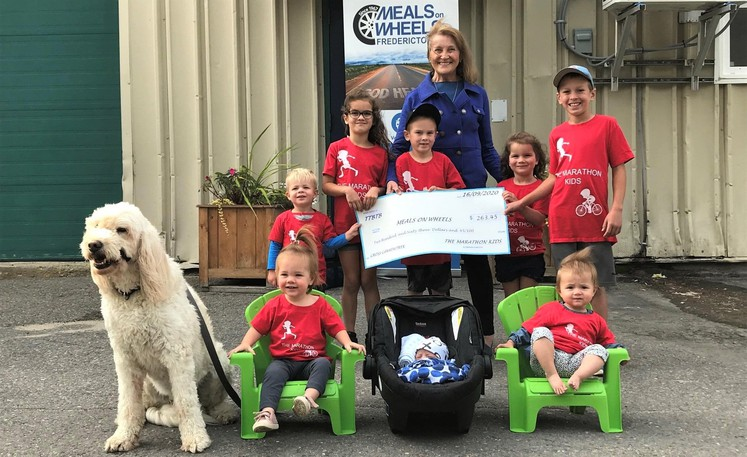 George Thompson's grandkids raised almost $1,300 for Meals on Wheels Fredericton by walking, biking and running during two separate 'travels' across Canada. Meals on Wheels executive director Betty Daniels accepts the first cheque from, front row, dog Jake, Rachel, Logan and Abby; middle row, Walter, Ava, Will, Olivia and Luke.