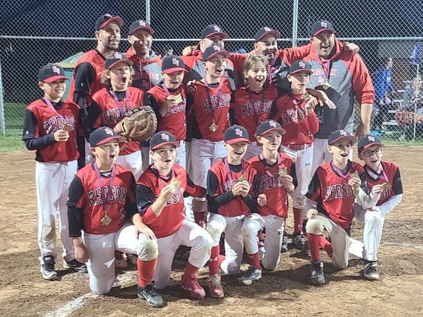 The KV Red Sox U11 AAA team celebrates winning the New Brunswick U11 AAA Provincial Championship. Front row (from L to R): Jude Ring, Owen Connolly, Calder Mackenzie, Quinn Clarke, Spencer Doucette, Lucas Trites. Second row (from L to R): Reid Crilley, Eric Somers, Cam Morrison, Sutter McQuaid, Carter Bizeau and Ian Ward-Donelan. Back row (from L to R): Coaches Ryan Morrison, Jason McQuaid, Shane Bizeau, Derek Doucette and Colin Ring.