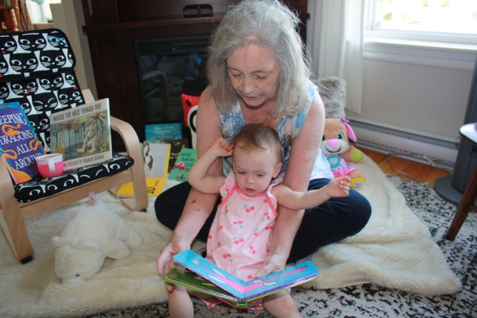 Grandmother Judy McAdam shares a story with granddaughter Ilsa, starting the process of sharing at only seven-and-a-half months.