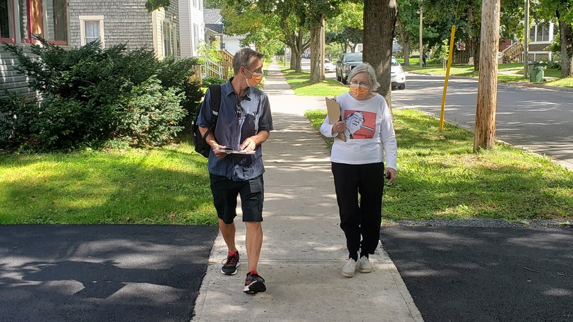 NDP candidate Shawn Oldenburg, pictured campaigning in Fredericton with party volunteer Glenna Hanley last week, has ended his door-knocking because of rising COVID-19 cases, according to a party official.