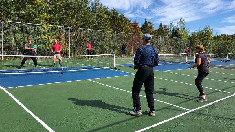 Members of the Carleton County Pickleball Club enjoy a match last year. The club recently finished resurfacing two of the four courts at the Covered Bridge Golf and Country Club, with plans to finish the rest in the coming weeks.