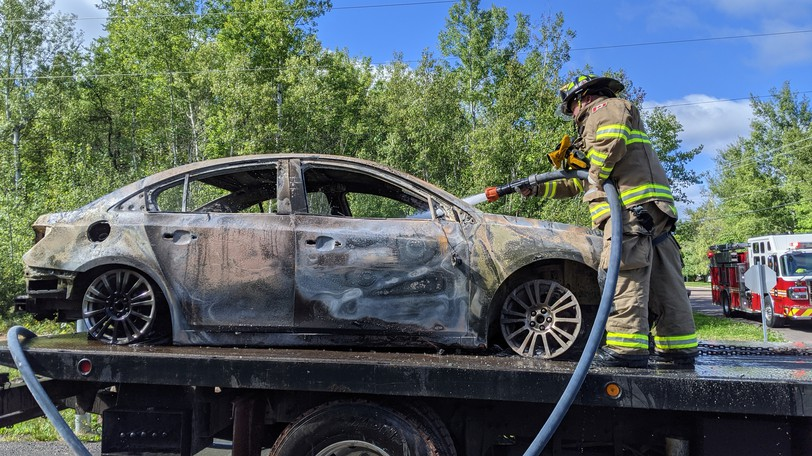 A Riverview firefighter sprays water into a car that was found abandoned and burned on the Trites Road extension Saturday morning.