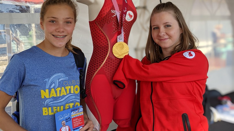 Gold medal swimmer Danielle Dorris, right, poses with another young swimmer, Sophie Landry, at the Moncton Market Saturday morning. Dorris won a gold and silver medal at the Paralympic Games in Tokyo last month.