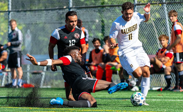 UNB Reds' Keji Adeniyi makes a tackle on Dalhousie Tigers attacker Enrico Rodriguez during AUS men's soccer conference action Saturday at Wickwire Field in Halifax. The Reds won 1-0. UNB blanked Acadia 2-0 on Sunday.
