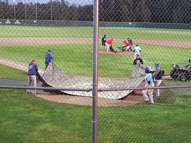 Grounds crews lay tarps over home plate and the pitcher's mound Sunday at Waldo Henderson Memorial Field in Miramichi as a thundershower forced the New Brunswick Intermediate A Baseball Championship final between the Dieppe Cardinals and Fredericton Jack's Pizza Expos to be postponed.