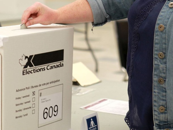 A voter places her ballot in the ballot box in this file photo.