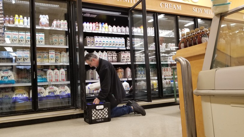 Blake Snodgrass stocks a dairy fridge at Atlantic Superstore on Monday. The plastic jugs being shelved were all made in Saint John at Bercon Atlantic.