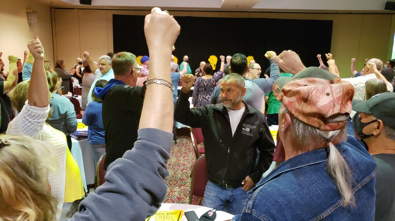 """Bargaining teams with the Canadian Union of Public Employees shout """"so-so-so, solidarity!"""" at a recent meeting in Fredericton about their contract negotiations with the provincial government."""