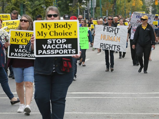 Protesters march in a demonstration against COVID-19 vaccine passports. Ken McGeorge writes that demonizing those who are vaccine hesitant is counterproductive.