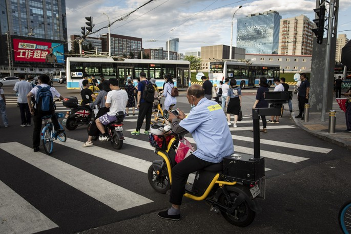 Commuters wait at a traffic intersection in Beijing on Aug. 25, 2021.