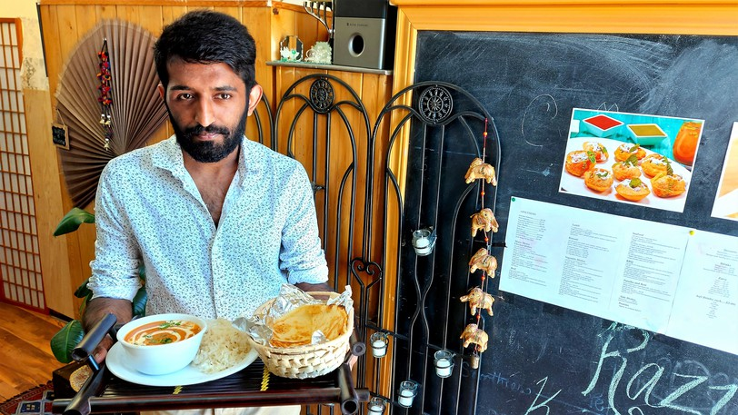 Taimoor Shahaid holds up an order of paneer butter masala with cumin rice and naan at Razia Kitchen on York Street in Fredericton. He co-owns the restaurant with his mother, Razia Sultana.