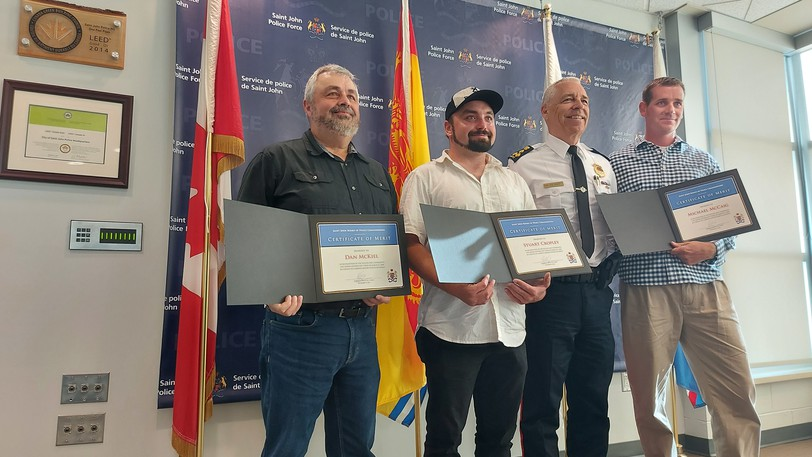 Dan McKiel, Stuart Cropley and Michael McCaig stand with Saint John Police Chief Robert Bruce as they were recognized for their rescue efforts more than a year ago. Fellow rescuer Quentin Turnbull was unable to attend the ceremony.