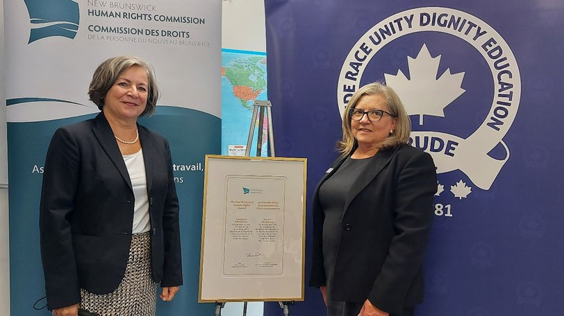 Claire Roussel-Sullivan, chair of the New BrunswickHuman Rights Commission, presents this year's New Human Rights Award to PRUDE Inc. Accepting the award on behalf of PRUDE is Karen Hachey, chair of PRUDE's board of directors.