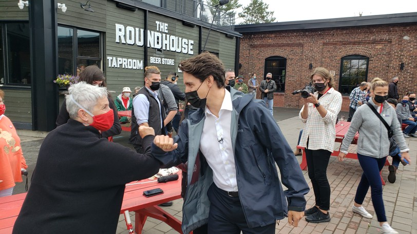 Liberal Leader Justin Trudeau bumps arms with a supporter at The Picaroons Roundhouse in Fredericton on Wednesday.