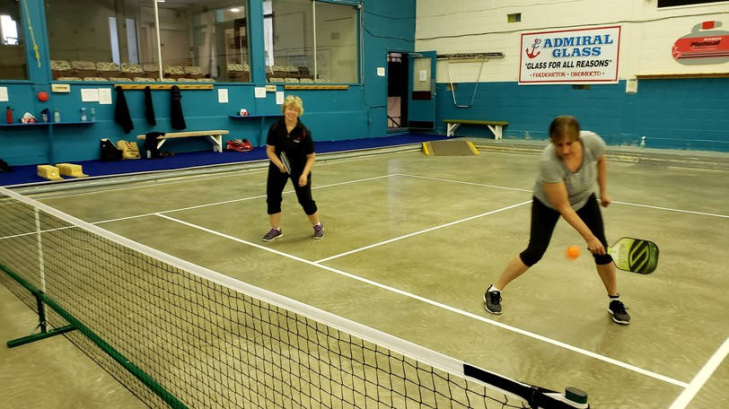 Chris MacLoon, left, and Louise Steward, right, play pickleball at the Grant-Harvey Centre. The Fredericton Pickleball Club match is raising $257,000 to build six new outdoor clubs, and wants the city to provide the land for the project.