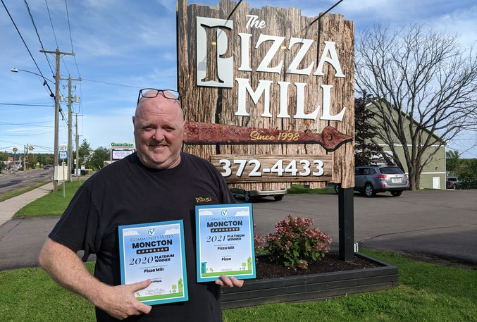 Pizza Mill owner Dave Kitchen proudly holds his back-to-back Community Votes Moncton Platinum awards for best pizza in Metro Moncton. The Salisbury pizza place has been a mainstay in the village for 23 years.