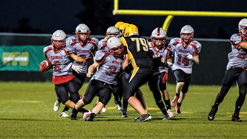 Saint John High Greyhounds' Ty Dalling (2) gains yardage as his teammates hold back Ethan McIntyre (79) of the FHS Black Kats during the Greyhounds' 40-0 road win Thursday.