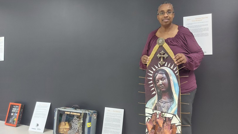 Rhonda Simmons holds up one of her pieces at the Mind, Body, Spirit of the Enslaves exhibition.