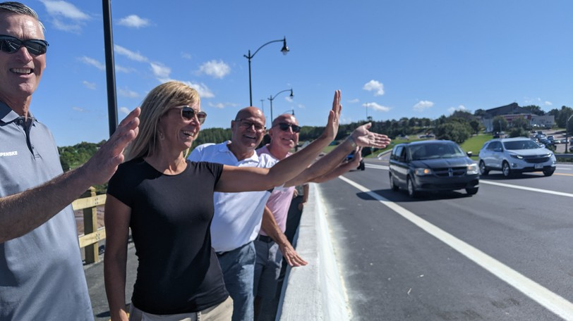 Derrick Hebb, Susan Hebb, Tim Durelle and Ronald LeBlanc of Riverview wave to cars as they pass by on the new bridge over the Petitcodiac River Friday.