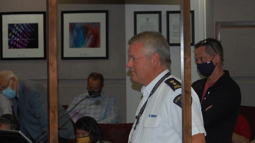 Supt. Ron DeSilva, acting officer in charge for Codiac Regional RCMP, standing at the podium, fields questions from councillors on Sept. 20, 2021, during a meeting of Moncton city council, following a presentation by Cameron Street resident Dereck Slattery, shown at right.