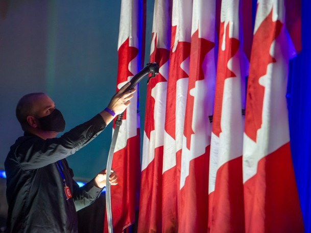 A person steams the Canadian flag at Oshawa's Tribute Communities Centre in preparation for Erin O'Toole's election night prior to results of the 2021 federal election.