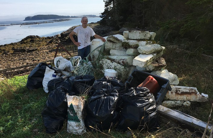 Carl Duivenvoorden stands beside one of the caches of trash he collected during his Terry Fox Run beach cleanup on the weekend.