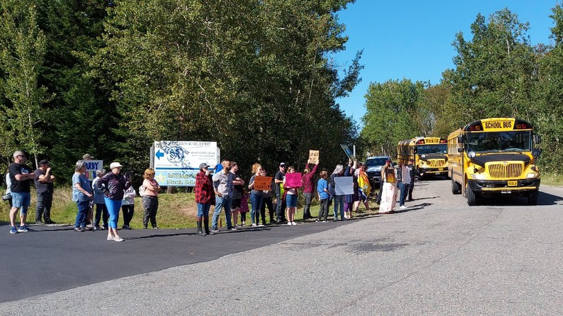 Buses with school children drove by the group of protesters outside of the Anglophone South School District's office on Tuesday afternoon.