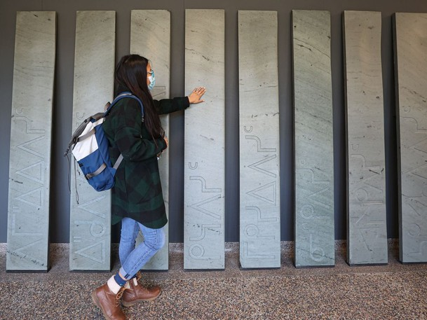 A University of Saskatchewan student feels the grooves on a new art installation at the Gordon Snelgrove Gallery where 13 of the old stone steps from the Thorvaldson building have been reclaimed, and carved with Cree syllabics to highlight the 13 moons of the lunar cycle, as part of the anohc kipasikonaw/we rise/niipawi art project. Photo taken in Saskatoon on Tuesday, Sept. 21, 2021.
