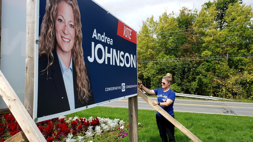 Unsuccessful Fredericton Conservative candidate Andrea Johnson tears down a campaign sign on Woodstock Road on Wednesday afternoon.