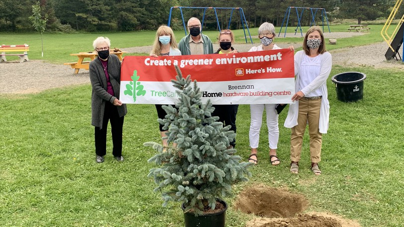 Members of the Brennan family donate a blue spruce tree to be planted at Florenceville Elementary School on Wednesday. From left are Ann Brennan, Rayanne Brennan, GAIA club leader Teena Bishop, Terry Hunter andVal McCowanof the Florenceville-Bristolbeautification department, Valerie Carmichael, Anglophone West community engagement coordinator; and Florenceville Elementary Principal Sarah Maher.