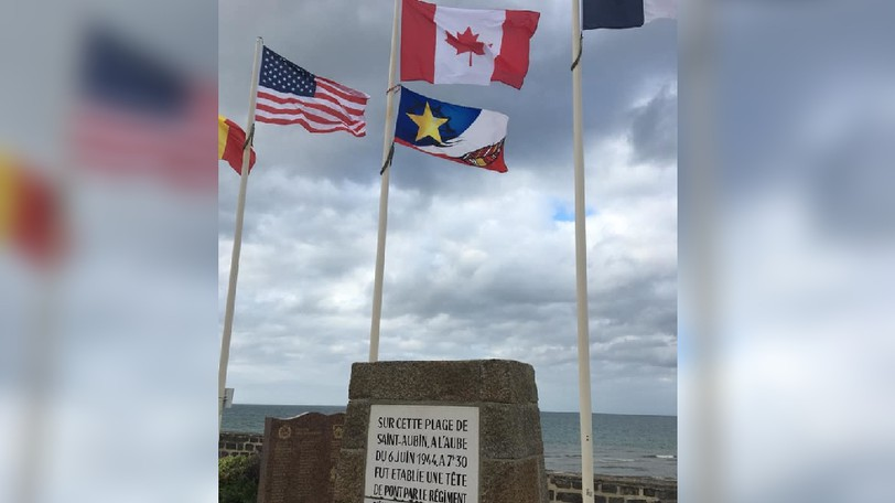 The flag of Nigadoo, near Bathurst, now flies near Saint-Aubin-sur-Mer, France to honour Acadian and Mi'gmaq wartime veterans. The town is part of the landing site known as 'Juno Beach' on the June 6, 1944 D-Day landings. A plaque also honours Canadian contributions, including New Brunswick's own North Shore Regiment.
