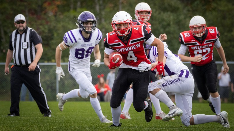 Riverview High Royals' Hunter Robinson (No. 4) runs the ball against the Moncton High Purple Knights during a New Brunswick High School Football League game on Saturday in Riverview.