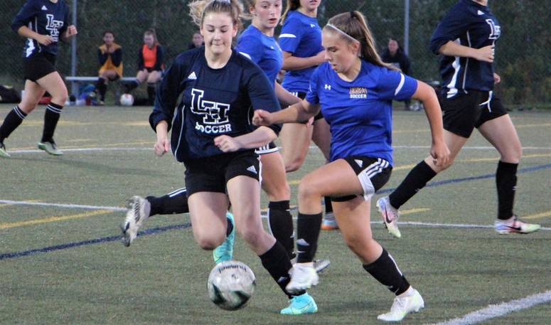 Alex Clark, left, of the Leo Hayes Lions varsity girls soccer team, fights for possession of the ball during a recent game against Ecole Sainte Anne. The Lions are hosting an eight-team tournament Friday and Saturday.