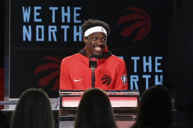 Smiling Raptors forward Pascal Siakim speaks at media day  on Monday.