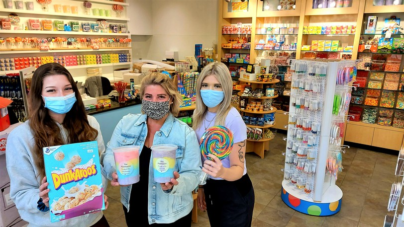 Frolic Confectionary co-manager Kristie Fowler, middle, and employees Riley Reggler, left, and Emma Sullivan, right, hold up some products for sale in the new candy store in Fredericton's Regent Mall.