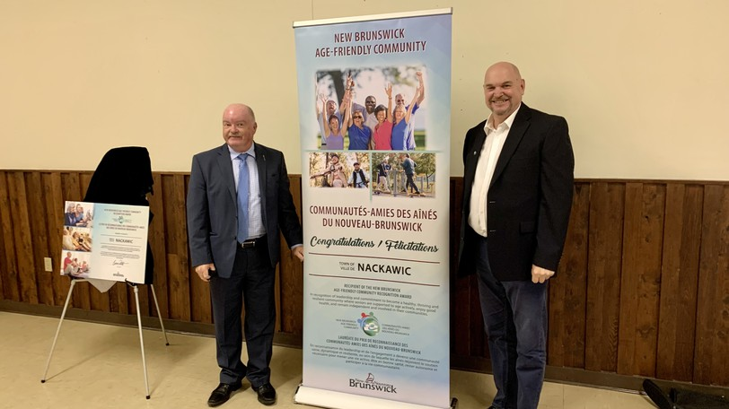 Minister of Social Development Bruce Fitch, left, and Nackawic Mayor Ian Kitchen unveil the banner for Nackawic's designation as an age-friendly community.